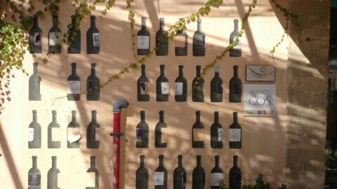 fresco's van wijnflessen op buitenmuur bij Cos